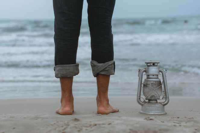 person standing on shoreline beside gray tubular lantern