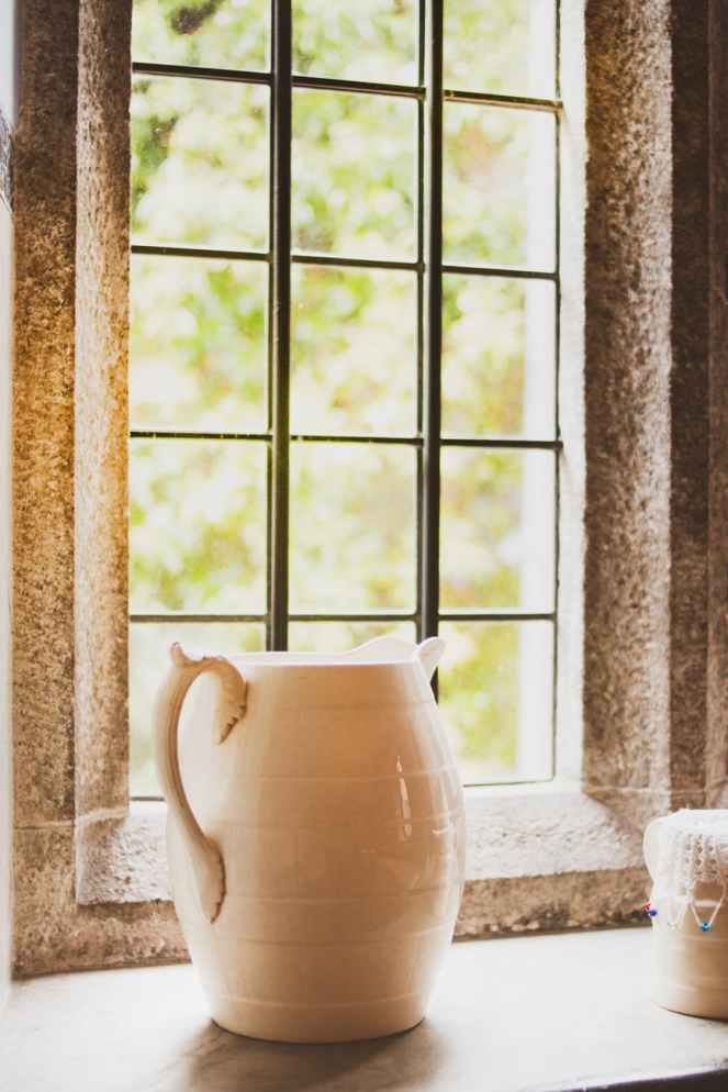 white ceramic pitcher next to window